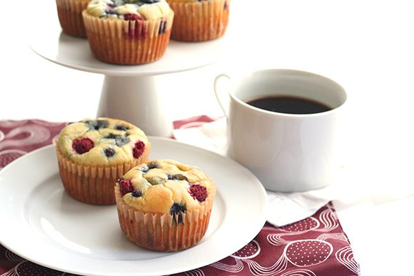 a white plate holding two fresh berry-packed low carb breakfast muffins made from grain-free pancake batter