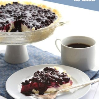 Blueberry cheesecake on a white plate with a blue napkin and a cup of coffee