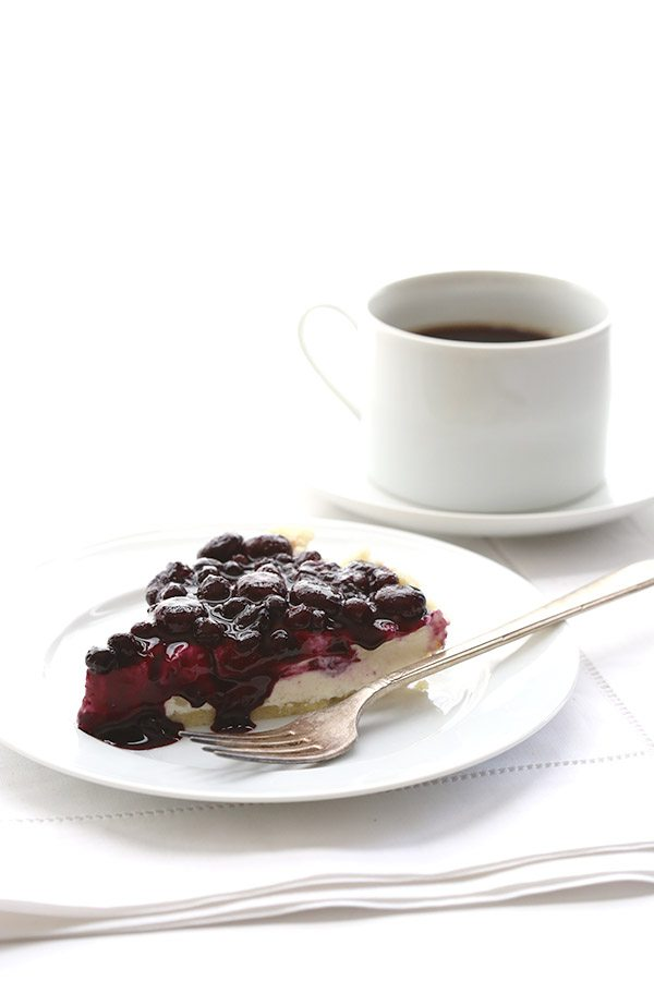 A slice of no bake blueberry cheesecake with blueberry topping on a white plate