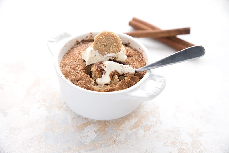 A single snickerdoodle mug cake with a spoon digging into it, with two cinnamon sticks in the background.