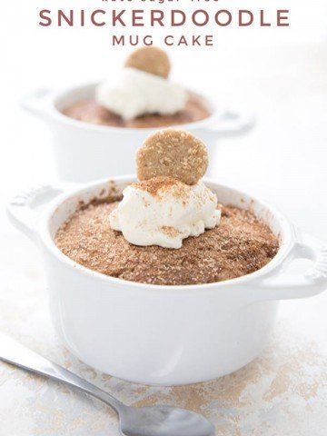 Titled image of two keto snickerdoodle mug cakes in white ramekins with whipped cream and mini cookies on top.