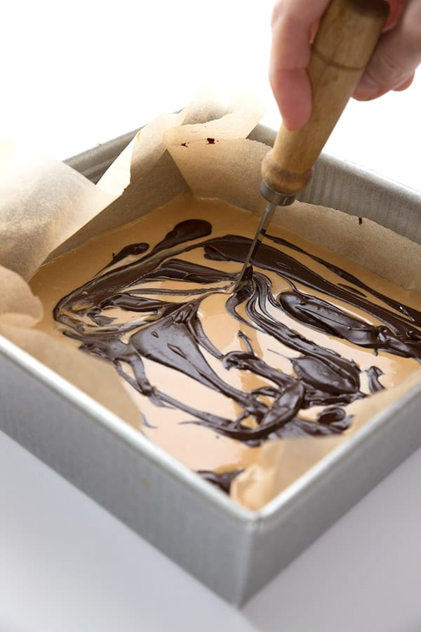 Using a knife to swirl together low carb peanut butter fudge with dark chocolate