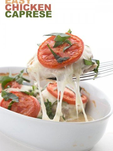 Easy Keto Caprese Chicken on a spatula with melted cheese stretching as it's pulled away from the dish
