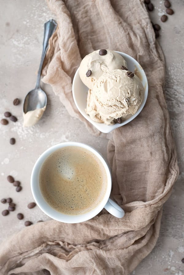 Top down photo of a bowl of keto coffee ice cream with a cup of coffee on a tan table.
