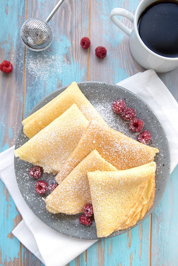 Top down photo of almond flour crepes with a cup of coffee and raspberries