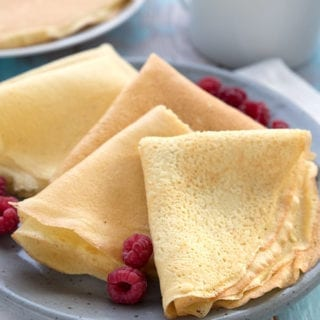 Keto almond flour crepes folded up on a grey plate, with a cup of coffee in behind.