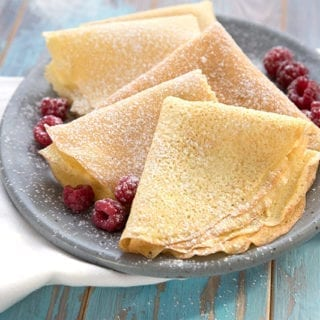 Keto crepes on a grey plate with a white napkin.