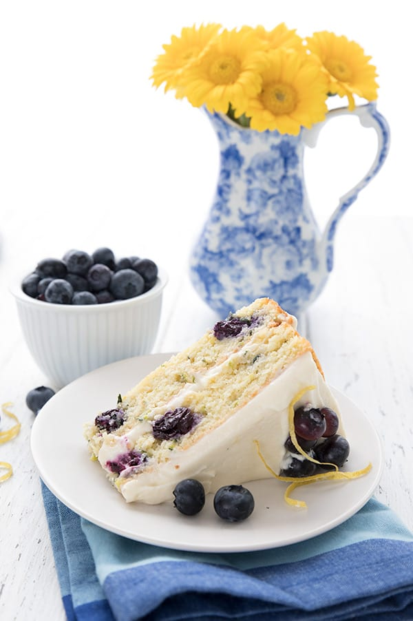 A slice of lemon blueberry zucchini later cake on a white plate with a vase of yellow flowers in the background.