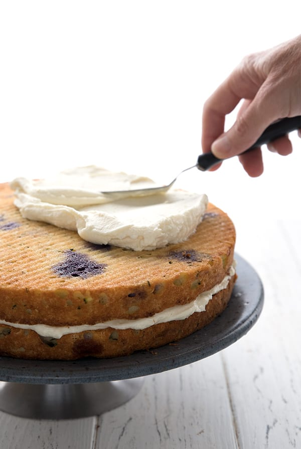 Spreading lemon cream cheese frosting on a keto blueberry lemon layer cake