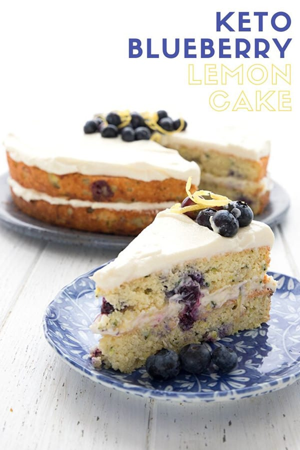 Titled image with a slice of Keto Lemon Blueberry Zucchini Cake on a blue patterned plate, with the rest of the cake in the background