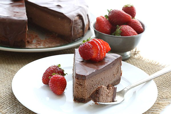 slice of Death By Chocolate grain free Cheesecake topped with sliced strawberries