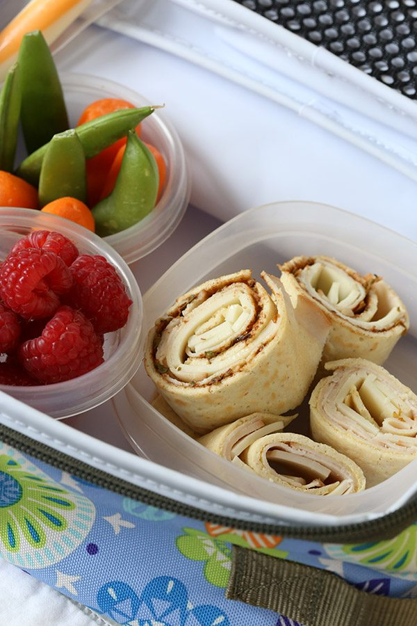 Healthy kid's lunch with low carb turkey pesto pinwheels, veggies and berries.