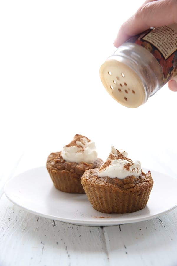 Pumpkin pie cupcakes with whipped cream on top, being sprinkled with pumpkin pie spice