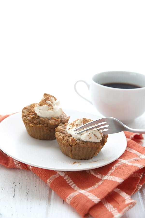 Low carb pumpkin pie cupcakes with a fork, an orange napkin, and a cup of coffee
