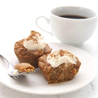 Two pumpkin pie cupcakes on a white plate with a fork and a cup of coffee