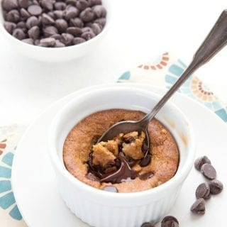 Titled image of a keto deep dish chocolate chip cookie in a white ramekin, with a spoon digging into it and a bowl of chocolate chips in the background.