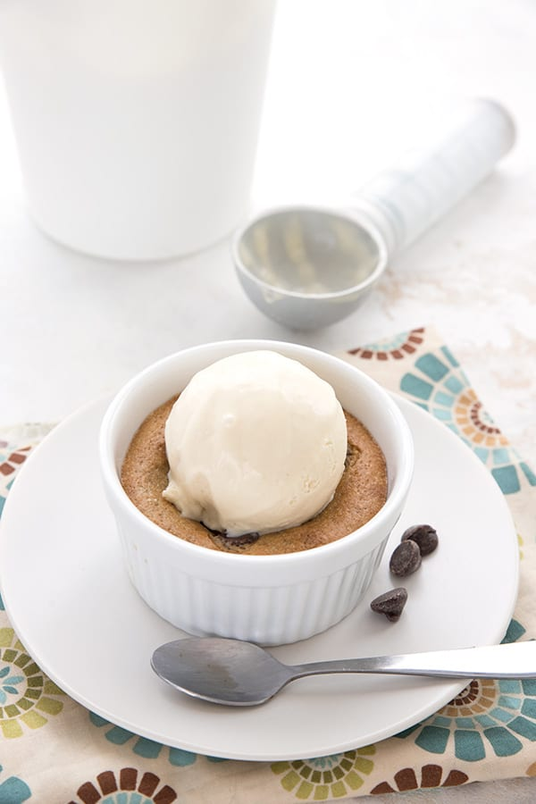 A gooey keto deep dish cookie with a scoop of ice cream on top. The container of ice cream and the scoop in the background.