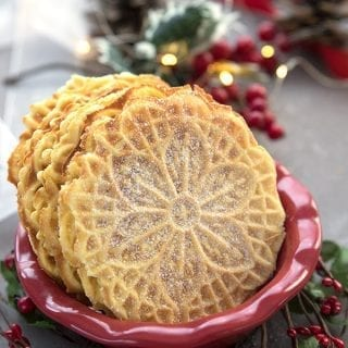 Keto pizzette in a red bowl, surrounded by holly and pine cones, with fairy lights in the background.