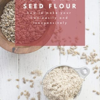 Top down photo of sunflower seed flour in a measuring cup on a white table.
