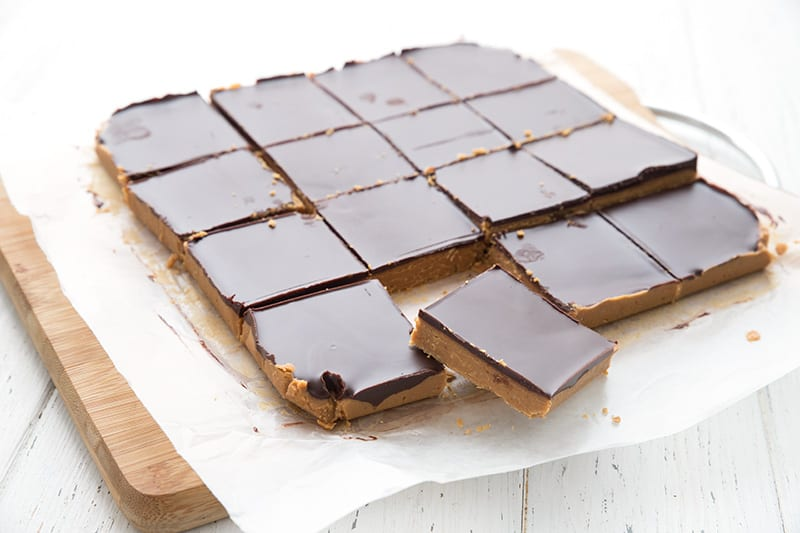 Keto peanut butter bars on waxed paper on a wooden cutting board.