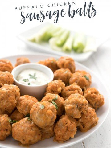 A plate of keto sausage balls with ranch dipping sauce in the center. There is a plate of celery in the background
