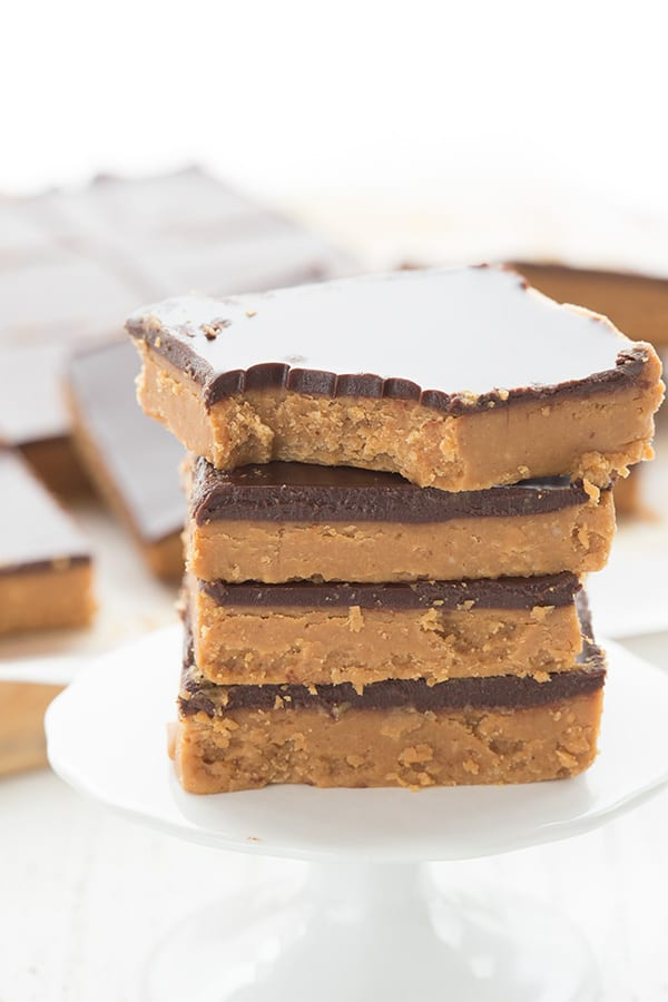 A stack of keto peanut butter bars on a small cupcake stand, with a bite taken out of the top one.