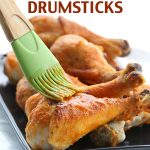titled image - Crispy Baked Buffalo Drumsticks - shown: drumsticks being basted with spicy Buffalo sauce