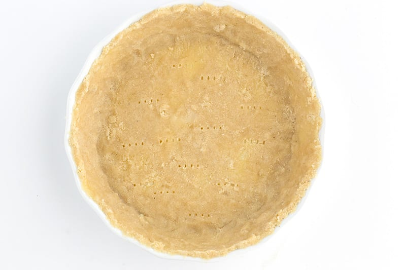 Top down view of unbaked keto pie crust in a ceramic plate.