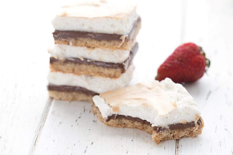 A stack of keto s'mores on a white table, with one s'mores bar in front and a strawberry in behind.