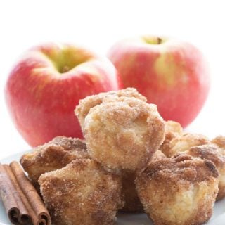 A plate of keto apple cider donut bites in front of two apples.