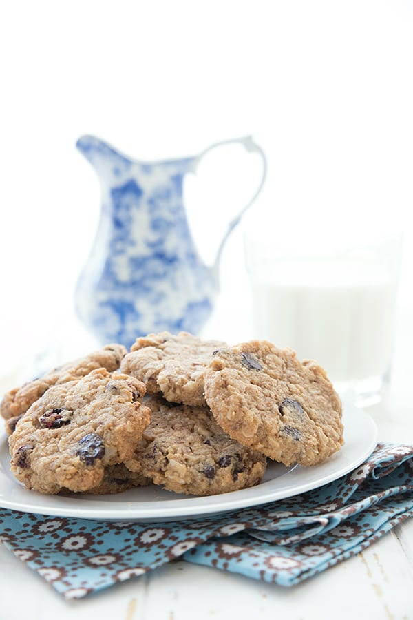 A white plate filled with sugar-free oatmeal cookies over a blue napkin. A glass of milk and a blue patterned pitcher in the background.