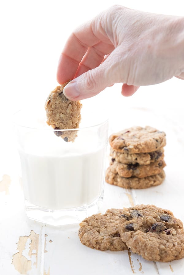 Dipping a piece of sugar-free oatmeal cookie into a glass of milk.
