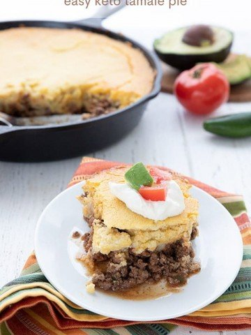 A plate of keto tamale casserole over a colourful napkin, in front of the skillet with the rest of the casserole.