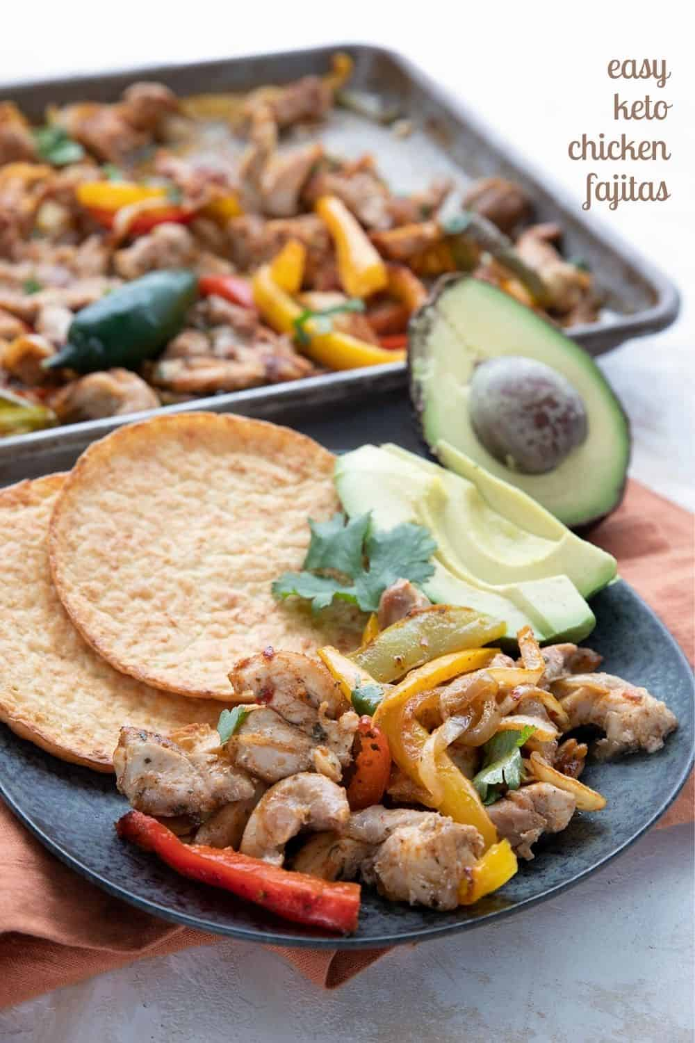 Titled image of sheet pan keto chicken fajitas, with some on a black plate in front of the sheet pan.