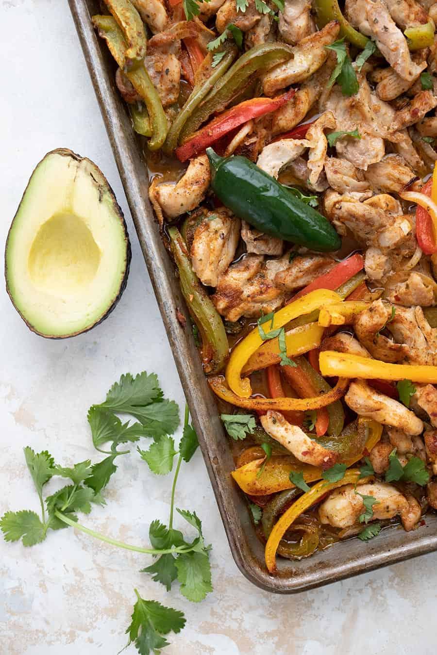 Top down image of sheet pan chicken fajitas with cilantro and avocado beside the pan.