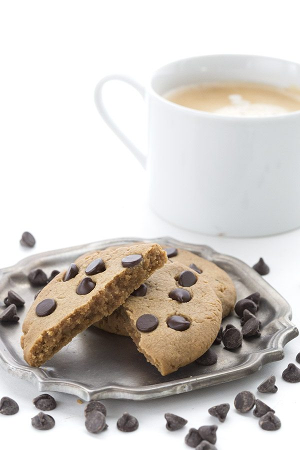 Two peanut butter chocolate chip cookies on a pewter plate with a cup of coffee behind it.