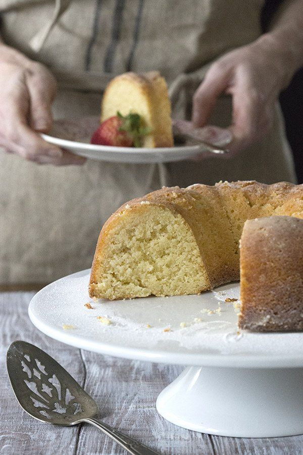 a low carb pound cake called Kentucky Butter Cake sitting on a white cake stand. Cake is sliced so you can see the inside