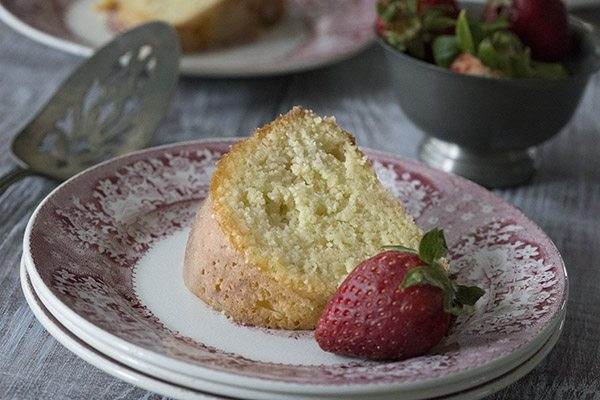slice of grain free Kentucky butter cake on a dessert plate, garnished with a fresh strawberry