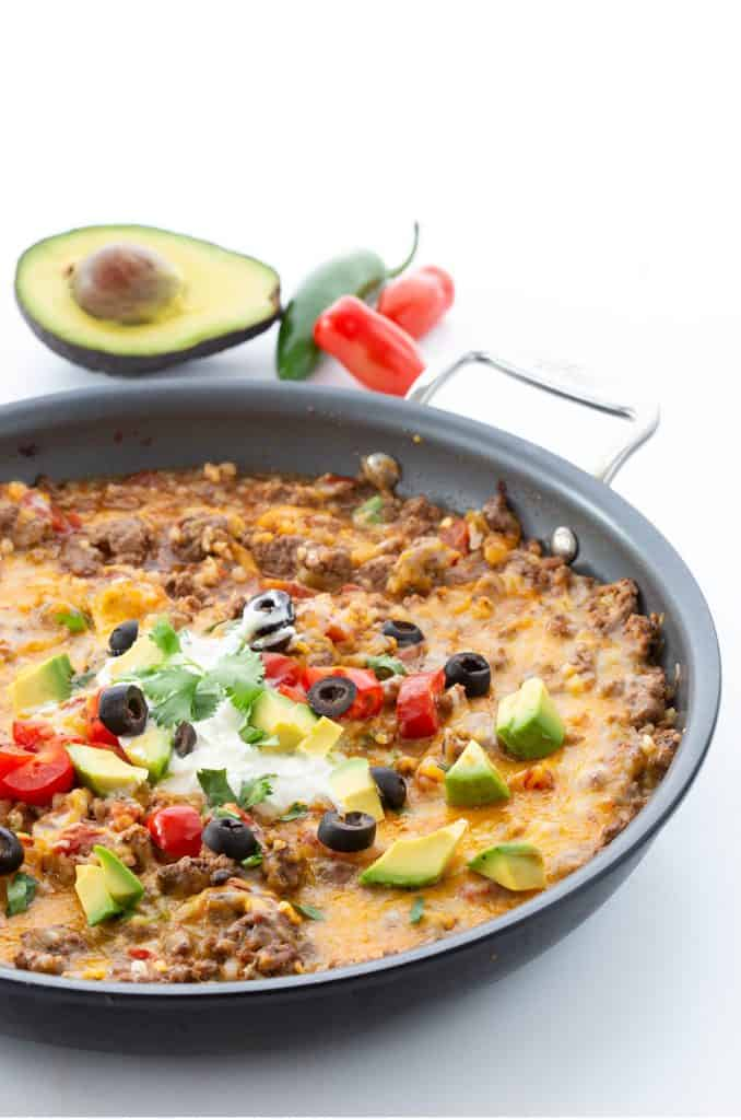 A pan filled with keto Mexican style cauliflower rice on a white background, with avocado, jalapeno, and tomatoes in the background.