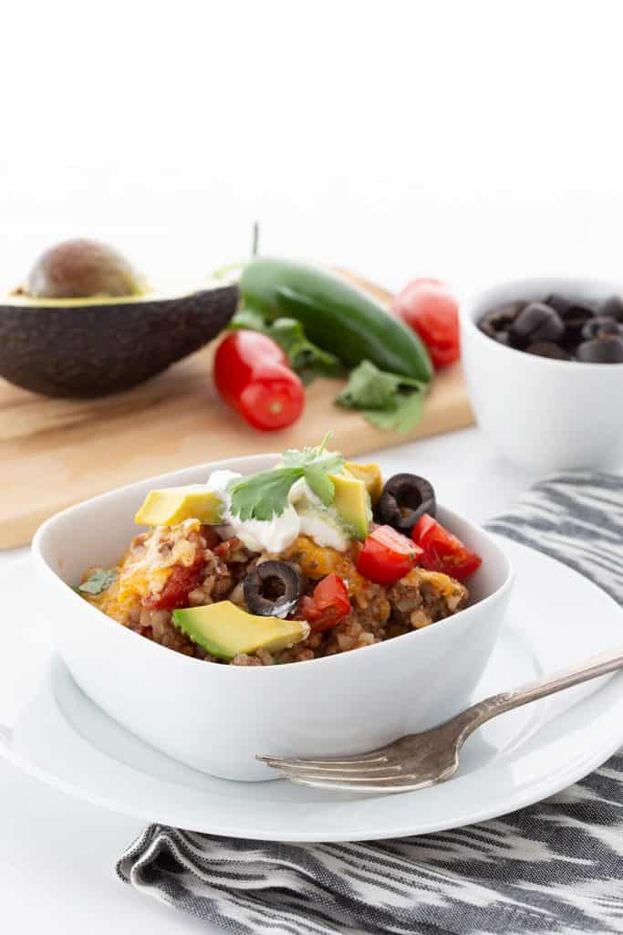 A bowl of Mexican Cauliflower Rice with avocado, tomatoes, jalapeños, and olives on a cutting board in the background.