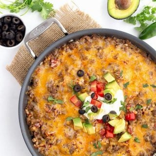Titled image: Top down view of a skillet filled with Mexican Cauliflower Rice, with avocado, cilantro, tomatoes, and olives scattered around.