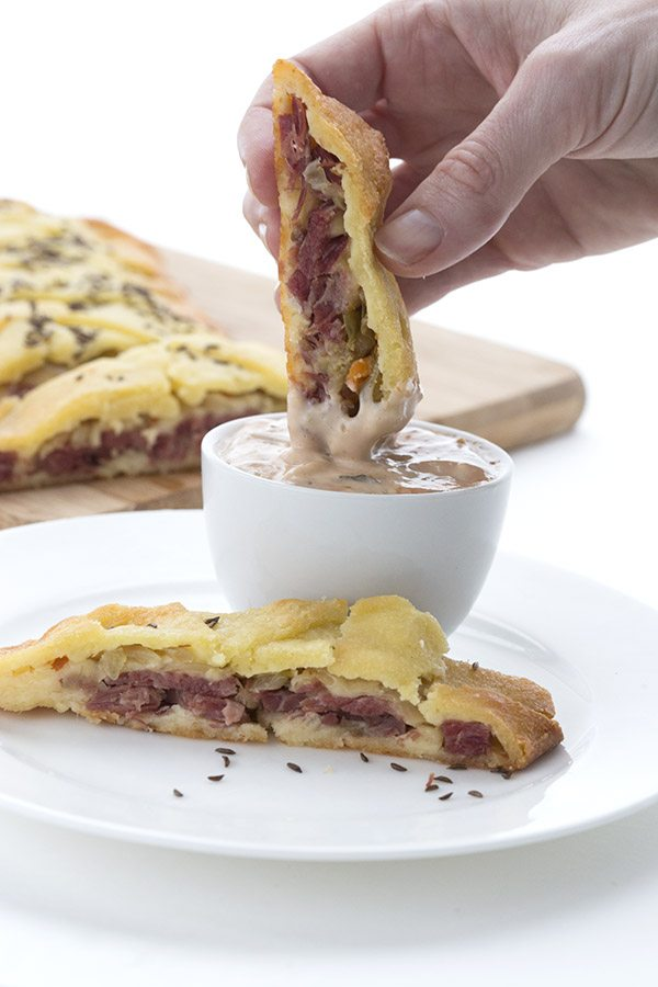 Dipping low carb Reuben Stromboli into sugar-free Russian dressing