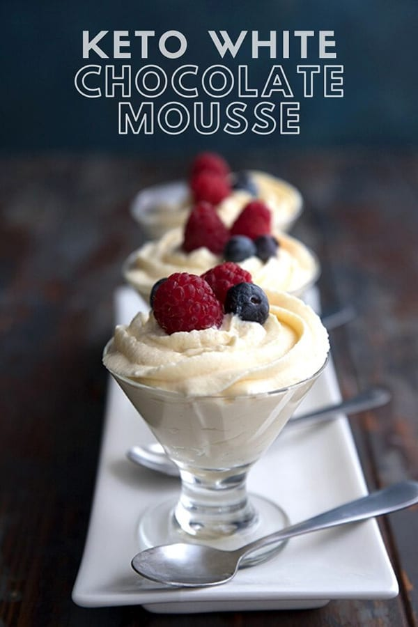 Titled Image: Three glass dessert cups filled with white chocolate mousse with berries on top, on a thin white platter.