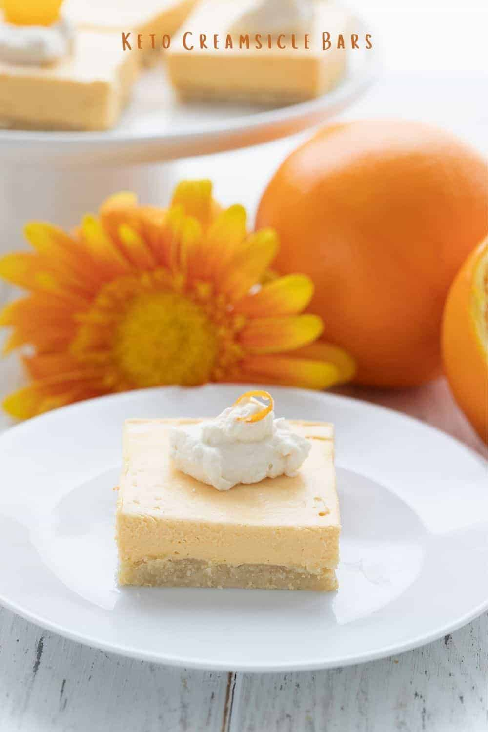 Titled image of a keto creamsicle on a white plate, in front of a cut up orange and some orange gerbera daisies