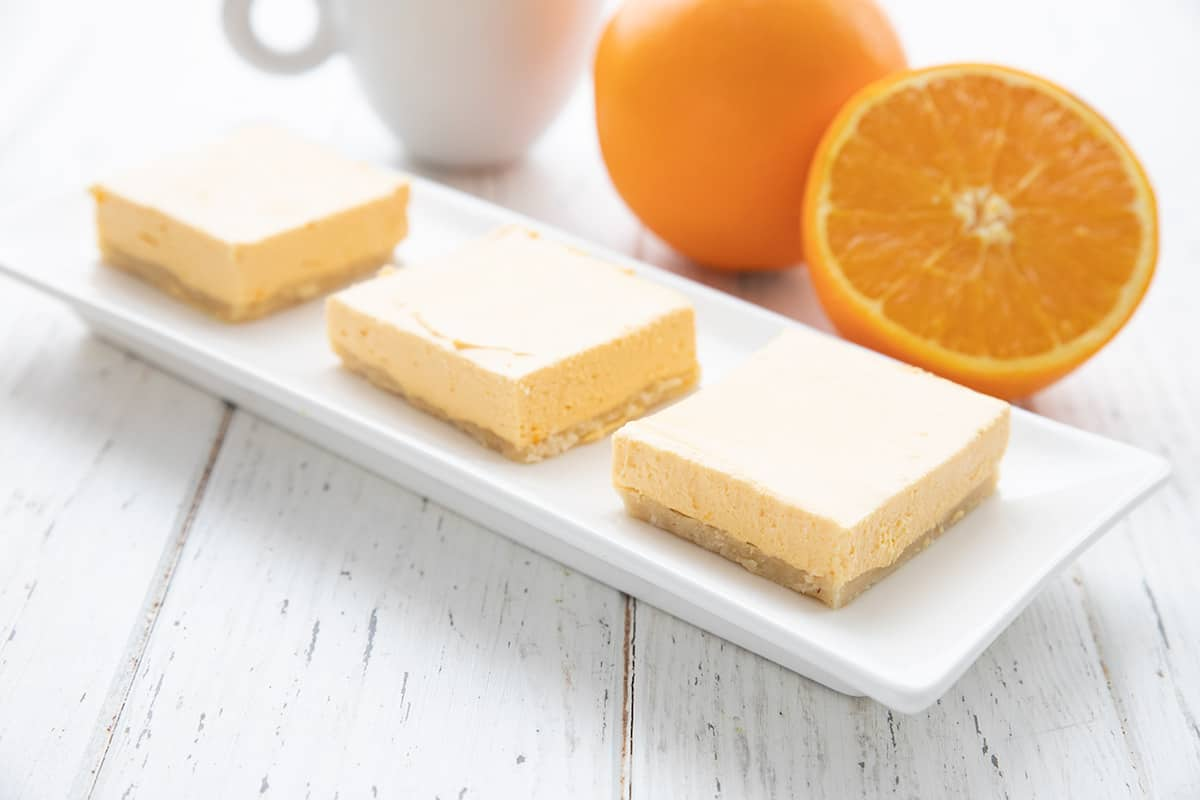Three creamsicle cheesecake bars on a long white tray in front of a cut up orange.