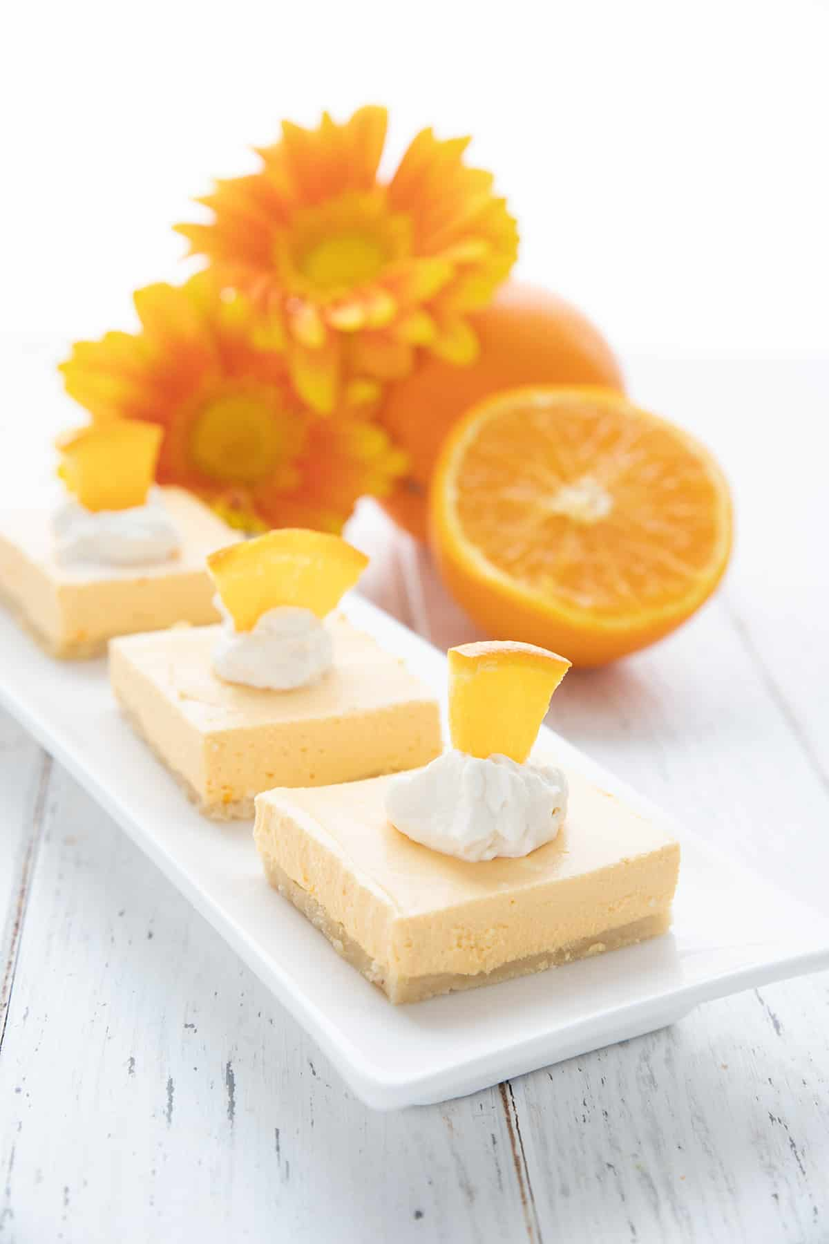 Three keto creamsicle bars on a long white try, topped with whipped cream and small slices of orange.