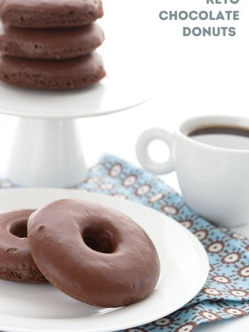 Titled image of keto chocolate donuts on a white plate over a blue patterned napkin, with a cup of coffee