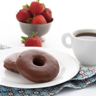 Keto chocolate donuts on a white plate with a cup of coffee and a bowl of strawberries