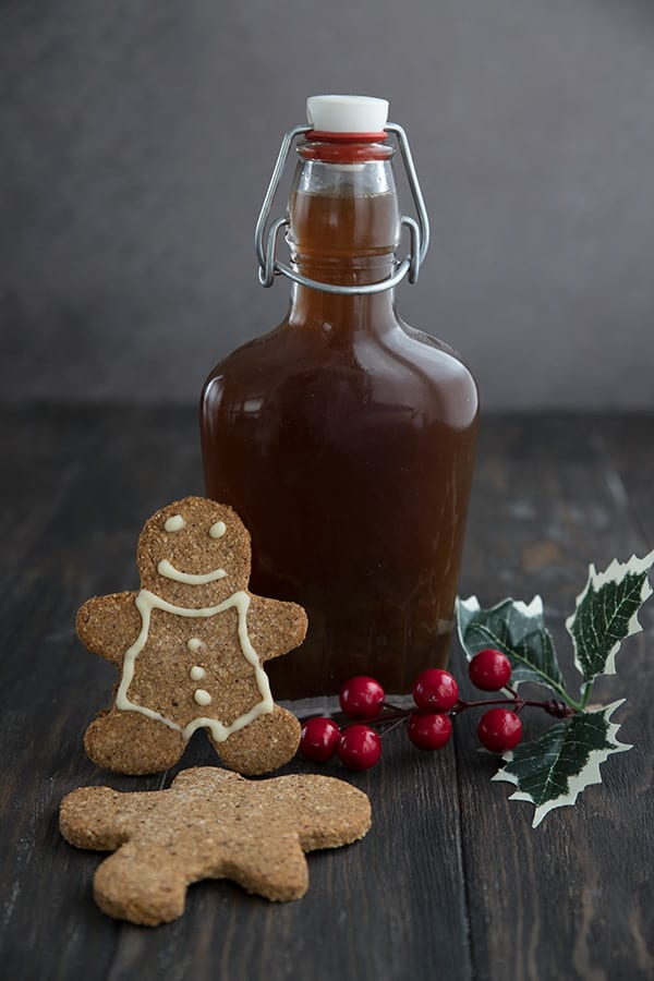 A bottle of keto gingerbread syrup on a wooden table with holly and two low carb gingerbread men cookies