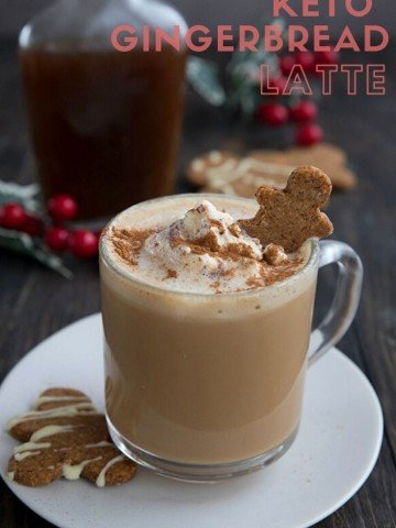 Keto gingerbread latte in a clear mug on a white plate with some keto gingerbread cookies